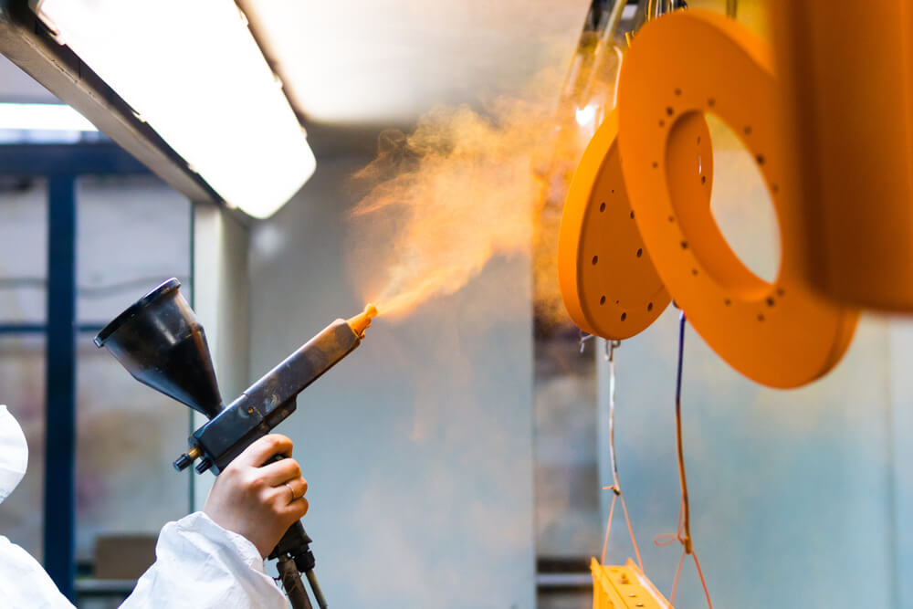 Person using powder coating on industrial equipment