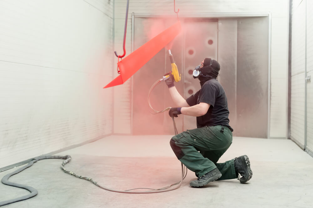 Man applying red powder coating to industrial equipment