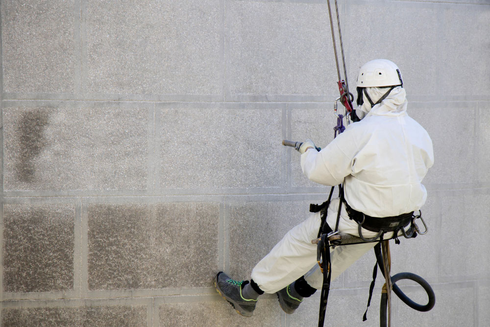 A Worker Sandblasting a Stone Building.