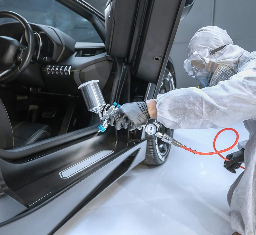 technician applying custom clear coat for vehicle