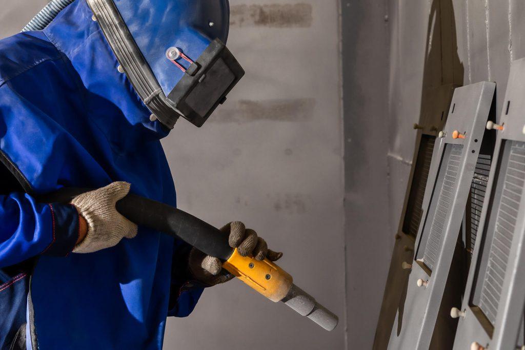 technician sandblasting steel doors