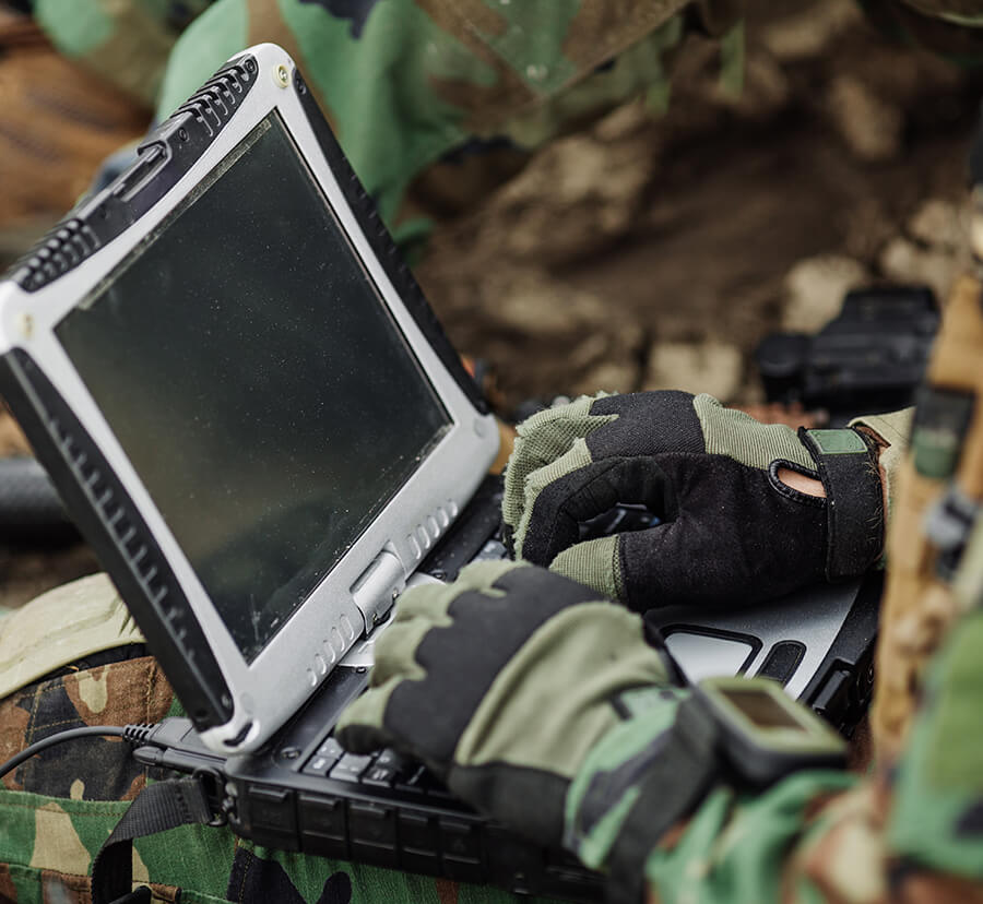 soldier works on custom coated laptop