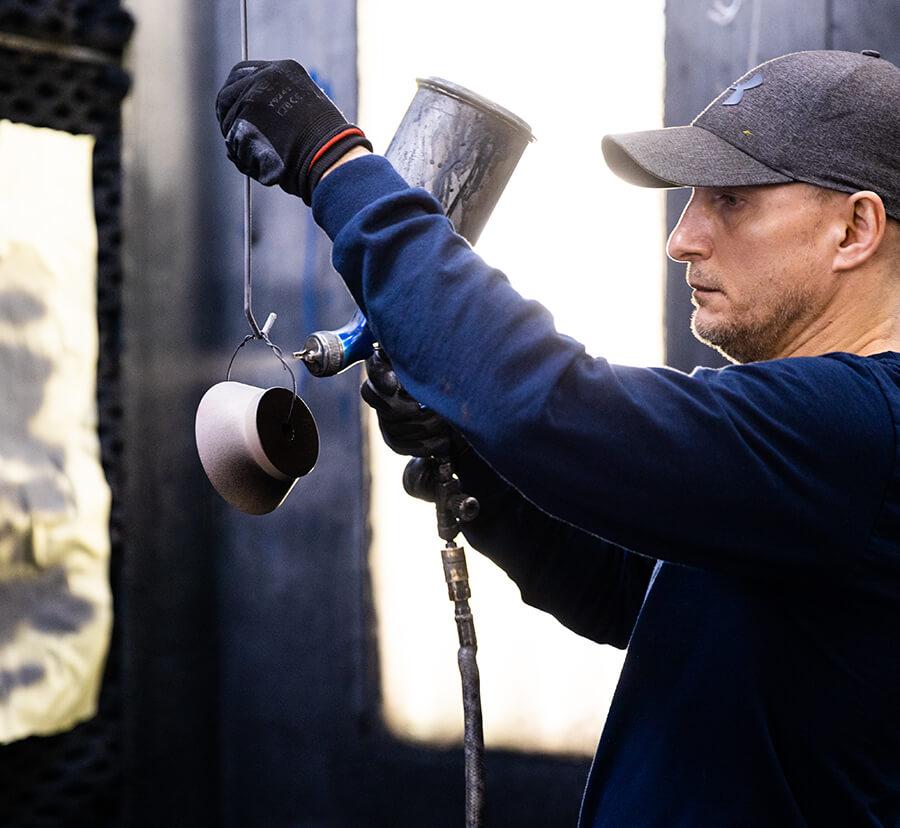 technician spray coating steel item